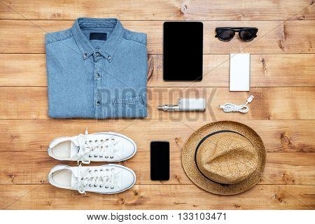 Travel concept shoes, shirt, mobile phone,mp3, usb, eyeglasses, tablet, hat, hookah on the desk