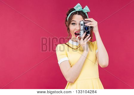 Happy beautiful pinup girl in yellow dress standing and taking photos using vintage camera over pink background