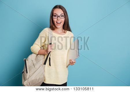 Beautiful cheerful smiling girl holding bagpack and notebook isolated on the blue background