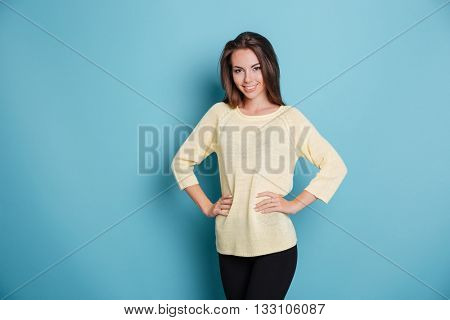 Portrait of a beautiful smiling girl with her arms on hips isolated on the blue background