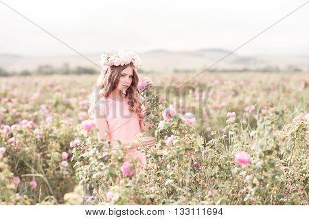 Beautiful teen girl 14-16 year old posing in rose field. Wearing wreath with flowers. Teenager hood.