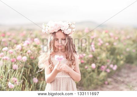 Cute baby girl 4-5 year old holding rose flower in meadow. Wearing floral wreath. Childhood.