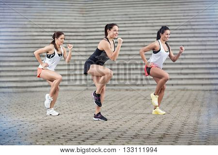 Group of young sportswomen doing aerobic exercises outdoor