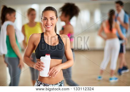 Young sporty brunette with ponytail after training with bottle of beverage