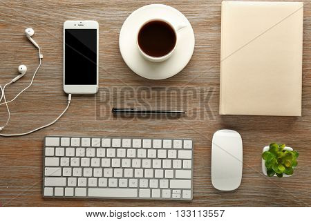 Workplace with mobile phone, peripheral devices and stationery on wooden table