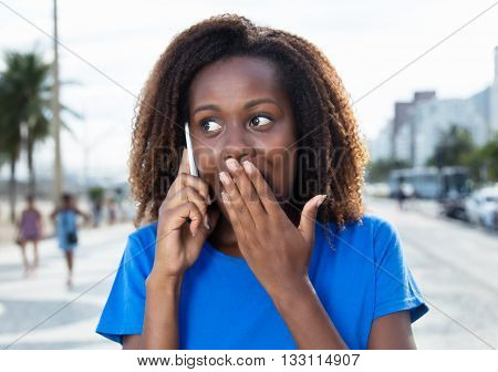 Surprised african woman in a blue shirt at phone outdoor in the city