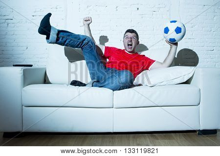 crazy fanatic man as football fan watching game on television wearing red team jersey celebrating goal happy and ecstatic jumping excited on sofa couch at home with ball