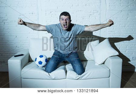 young man fanatic and crazy football fan watching television soccer match alone screaming happy celebrating scoring goal in glad and ecstatic face expression with ball on home couch