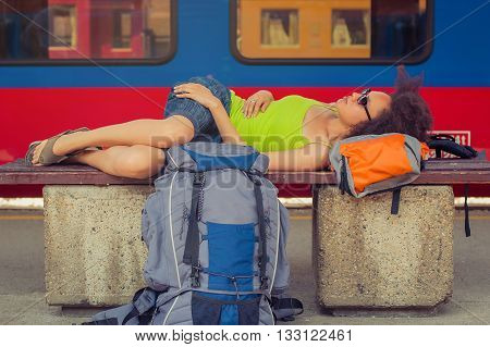 Beautiful female backpacker tourist napping on a bench and baggage at the station