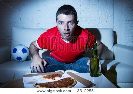 crazy fanatic man football fan watching football game on television wearing red team jersey suffering nervous and stress on sofa couch at home with soccer ball beer bottle and pizza