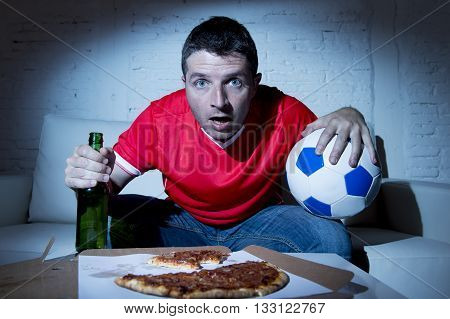 crazy fanatic man football fan watching football game on television wearing red team jersey suffering nervous and stress on sofa couch at home holding soccer ball drinking beer eating pizza