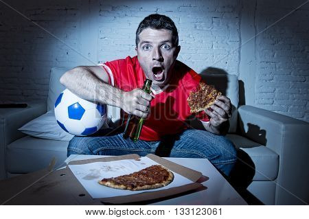crazy fanatic man football fan watching football game on television wearing red team jersey nervous and surprised on sofa couch at home holding soccer ball drinking beer eating pizza