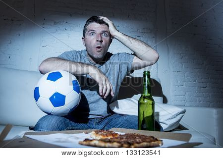 young fanatic man watching football game on television nervous and excited suffering stress on sofa couch at home with ball beer bottle and pizza looking anxious and crazy