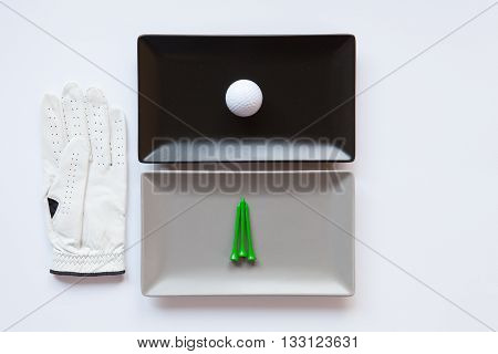 Different ceramic dishes with golf glove on over white background rectangle dish