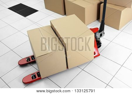 Manual pallet truck with carton boxes indoors poster