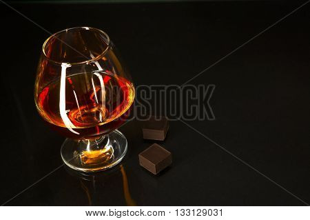 Brandy glass and chocolate on black background. Brandy glass. Cognac glass. Whiskey glass. Cognac france.