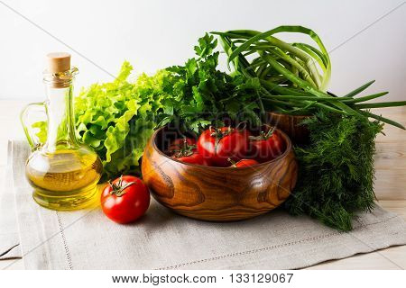 Fresh tomato in wooden bowl and olive oil. Ripe vegetables. Fresh vegetables. Healthy eating concept. Healthy eating. Vegetarian food.