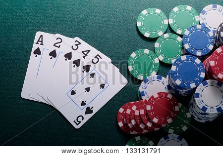 Casino chips and straight cards combination on the green table. Poker game