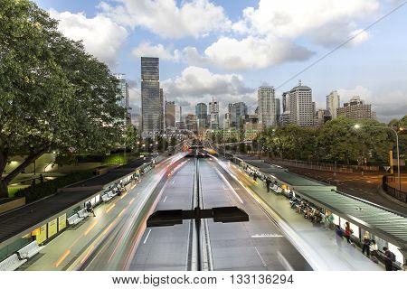 BRISBANE, AUSTRALIA - FEBRUARY 12 2014: Day to night transition of Brisbane cityscape and night busway rapid transit light trails.