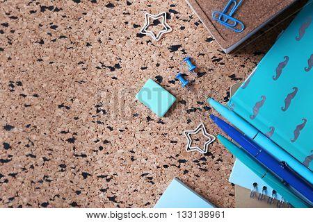 Stationery on cork board background.