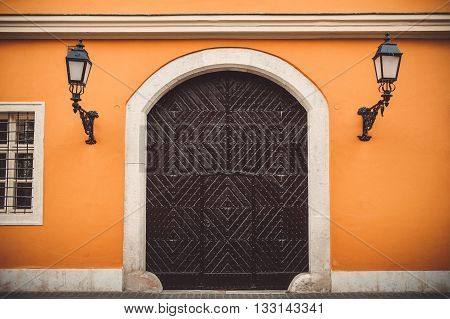 Old wooden door in orange wall with lanterns on the streets of Budapest Hungary.