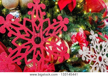 Christmas decoration assortment, featuring a large cardboard-made snowflake or ice crystal in red color among other ornamental assortment.