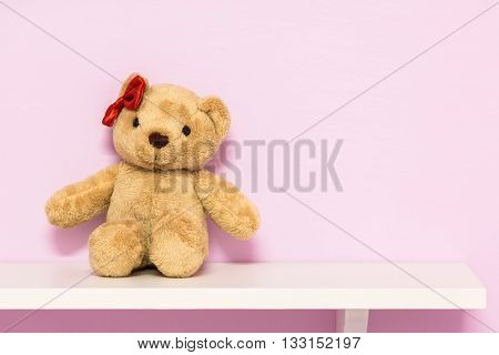 Classic teddy bear on shelf. Brown teddy on the pink background.