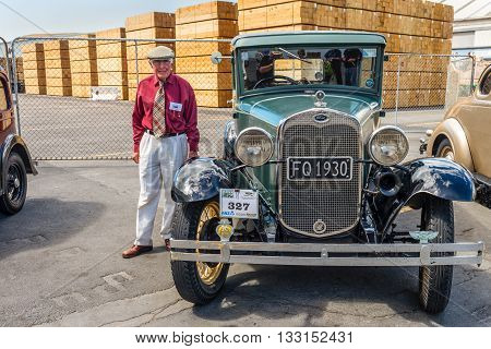 Napier New Zealand - November 19 2014: Classic vintage 1930 green saloon motor car and driver dressed in 1930s attire would chauffeur paying passengers around the quaint Art Deco seaside town of Napier on the North Island of New Zealand.