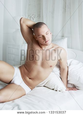 attractive young man resting in bed at home
