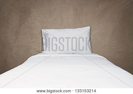 Close up white bedding and pillow on gray concrete texture background
