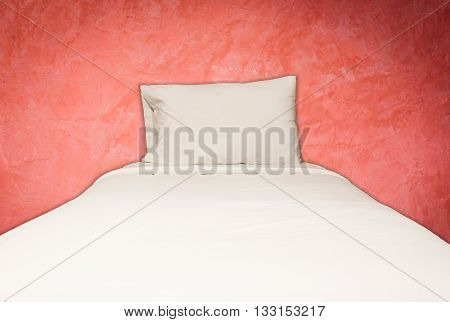 Close up white bedding sheets and pillow on red wall background