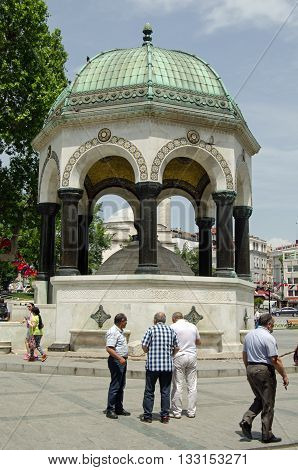 ISTANBUL TURKEY - JUNE 3 2016: Tourists and locals enjoying the sunshine beside the landmark German Fountain in Sultanhamet Istanbul. The monument marks the visit of Emperor Wilhelm II to the city in 1898.