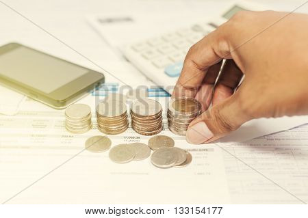 Close up of hand stacking silver coins with phone on paper bill Business finance and money concept Save money for prepare in the future Vintage style