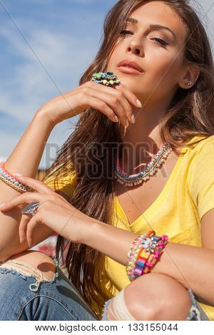 young urban woman with lot of summer jewelry portrait in the city closeup