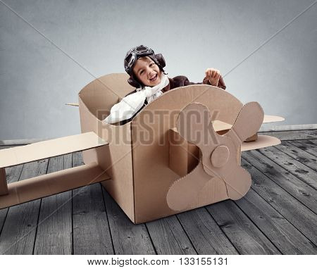 Boy wearing old-fashioned aviator hat, scarf and goggles flying a cardboard airplane in his imagination