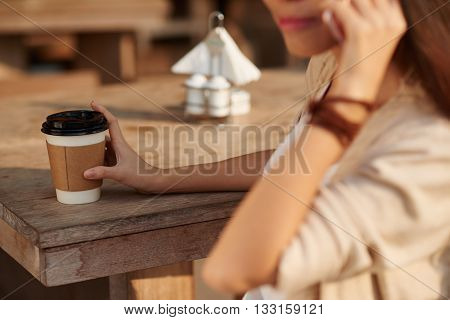 Cropped image of woman drinking take-out coffee and talking on phone