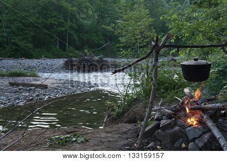 Black pot on a background of trees and river. Over the fire.