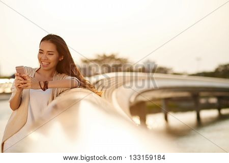 Smiling pretty woman standing on the bridge and reading message in her phone