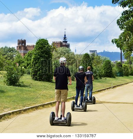 BARCELONA, SPAIN - MAY 30: Tourists taking a segway tour at the Parc de la Ciutadella on May 30, 2016 in Barcelona, Spain, with the Castell dels Tres Dragons in the background