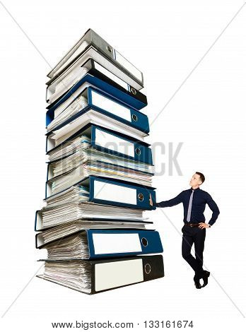 Young businessman stands beside the huge pile of folders with documents. Yearly corporate report. Isolated on white.