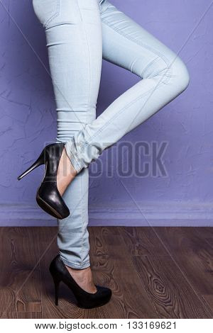 Leggy girl in black shoes with high heels on the wooden floor is lifting one leg