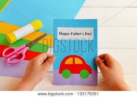 Card that said Happy father's day. Greeting card made by a kid. Child holding a greeting card for dad. Hand paper crafts. Set of colored paper, glue stick, scissors. Set for kids art implementation