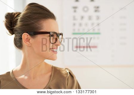 Modern health care. Profile portrait of happy young woman wearing eyeglasses in front of Snellen chart