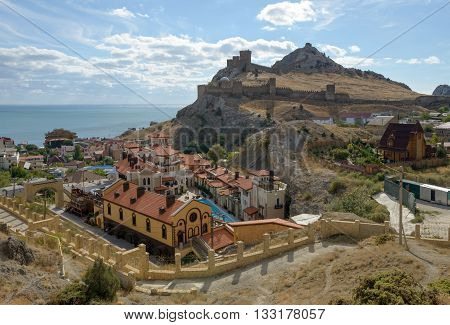 SUDAK, CRIMEA, RUSSIA - 08 OCTOBER: Bright afternoon sunlight is illuminating hillside of Genoese fortress and adjoining buildings of town on 08 October, 2015in Sudak, Crimea, Russia