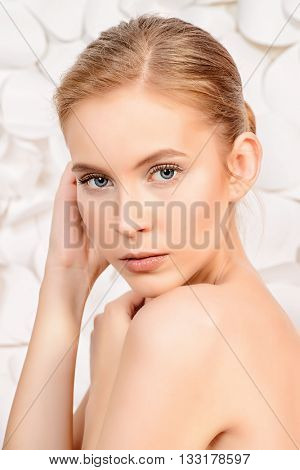 Portrait of a beautiful young woman with natural make-up over white floral background. Spa girl. Skincare, healthcare. Studio shot.