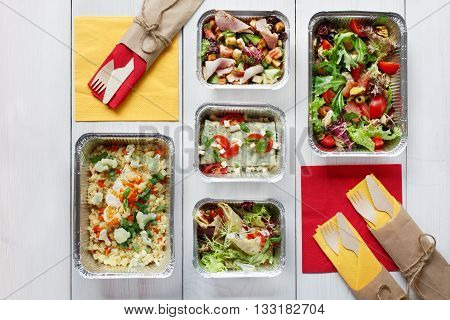 Healthy food delivery. Take away of natural organic low carb diet. Eat right concept, healthy food, clean food take away in aluminium boxes, vegetable salads and meat top view, flat lay at white wood