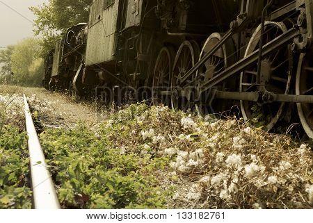 Low angle view of a retro train and railroad tracks for train transportation retro tone. Vintage green steam powered railway train.