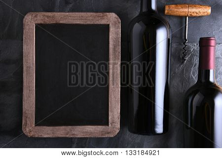 Top view of a blank chalk board for a wine list or menu with two wine bottles and old cork screw. Side light on a slate table.