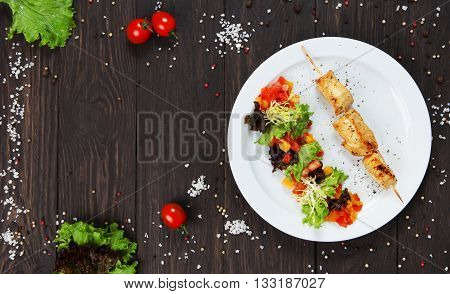 Healthy restaurant food. Creative cuisine. Chicken barbecue and vegetable salad. Meat bbq grill at wooden stick and salad with peppers and tomatoes. Restaurant dish served at white plate, closeup.