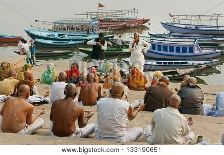 VARANASI, INDIA - JAN 1, 2016: Crowd of hindu people and the teacher gives a lecture about the proper rituals in life of a Hindu on January 1, 2016. Varanasi urban agglomeration had population of 1435113